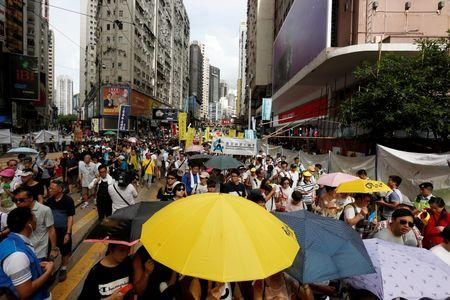 A protester carries a yellow umbrella, symbolizing the 2014 Occupy Central pro-democracy movement, during a protest march on the day marking the 19th anniversary of Hong Kong's handover to Chinese sovereignty from British rule, in Hong Kong July 1, 2016.  REUTERS/Bobby Yip