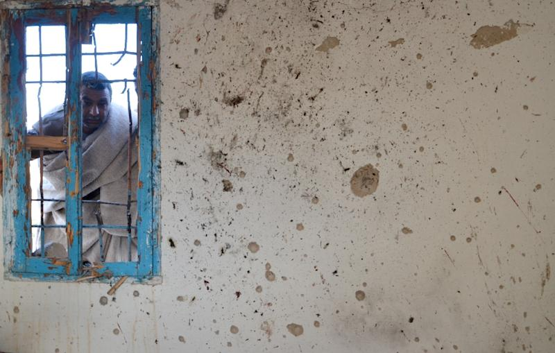 A Tunisian man looks through the window of a house in Benniri, just south of Ben Guerdane near the Libyan border, on March 9, 2016, where suspected jihadists were holed up and killed in a confrontation with Tunisian security forces overnight (AFP Photo/Fathi Nasri)