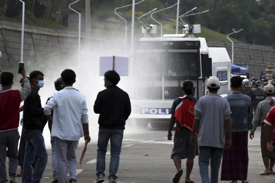 Demonstrators watch as police water cannon trucks as they retreat during a protest against military coup in Naypyitaw, Myanmar on Thursday, Feb. 18, 2021. Demonstrators against Myanmar's military takeover returned to the streets Thursday after a night of armed intimidation by security forces in the country's second biggest city of Mandalay. (AP Photo) (AP Photo)