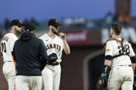 San Francisco Giants starter Alex Wood, center, talks to teammates Buster Posey (28) and Evan Longoria (10) and pitching coach Andrew Bailey, second from left, before pitching against the Texas Rangers during the sixth inning of a baseball game in San Francisco, Monday, May 10, 2021. (AP Photo/John Hefti)
