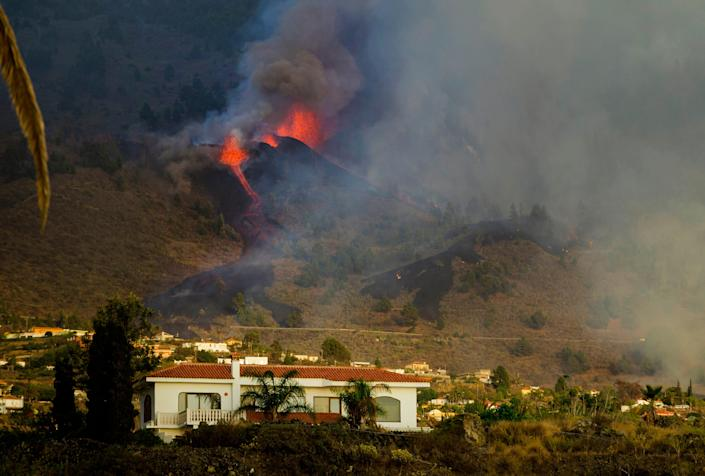 Lava flows from an eruption of a volcano at the island of La Palma in the Canaries, Spain, Sunday, Sept. 19, 2021. A volcano on Spain's Atlantic Ocean island of La Palma erupted Sunday after a weeklong buildup of seismic activity, prompting authorities to evacuate thousands as lava flows destroyed isolated houses and threatened to reach the coast. New eruptions continued into the night.