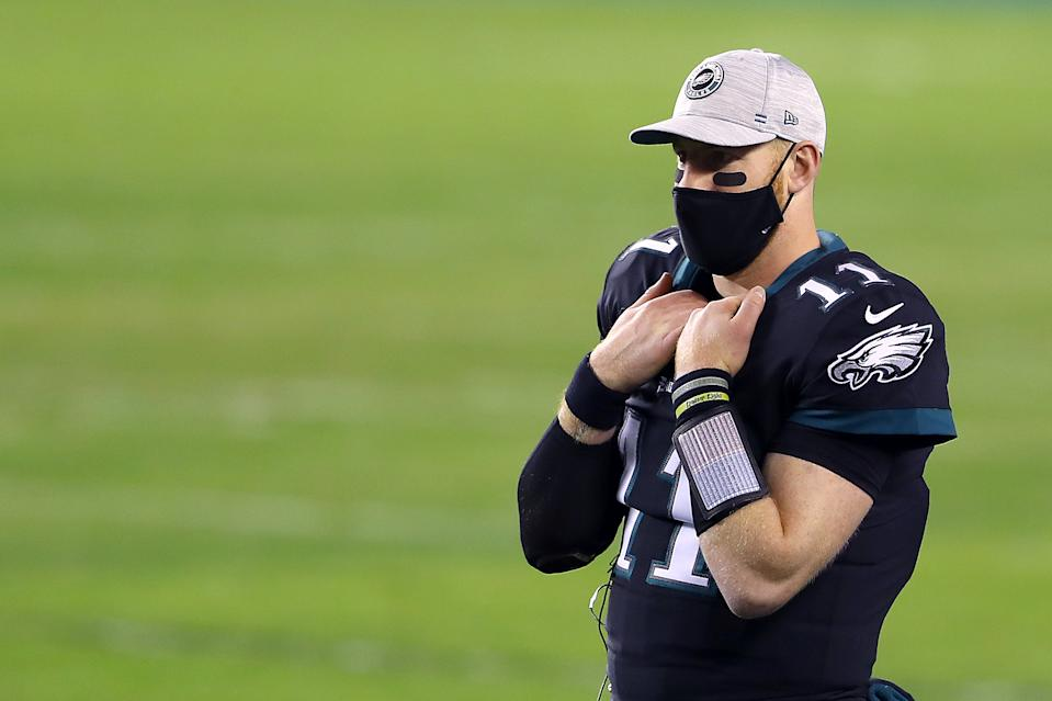 Carson Wentz wears a mask and ball cap as he looks on from the bench.