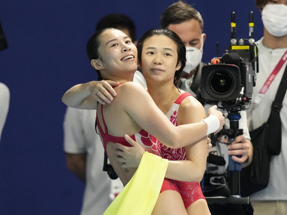 Shi Tingmao and Wang Han react after winning gold medals during the Women's Synchronized 3m Springboard Final at the Tokyo Aquatics Centre at the 2020 Summer Olympics, Sunday, July 25, 2021, in Tokyo, Japan. (AP Photo/Dmitri Lovetsky)