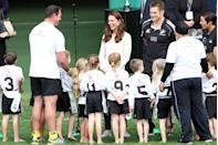 <p>Middleton attends a kid's rugby game in Australia. She's seen here laughing along with the little rugby players and their coach.</p>