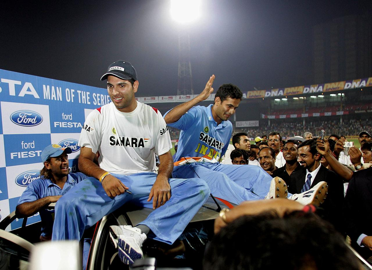 Yuvraj Singh (L) along with Irfan Pathan (R) sit on top of the car that was gifted to the man of the series on the final one day international cricket match against South Africa at the Wankhade Stadium in Mumbai, 28 November 2005.  India, who restricted South Africa to 221-6 after electing to field on the slow wicket, surpassed the modest target for the loss of five wickets with 15 deliveries to spare.  AFP PHOTO/Sebastian D'SOUZA.