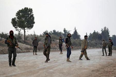 FILE PHOTO -  A file photo shows free Syrian Army fighters carrying their weapons as they stand on the outskirts of the northern Syrian town of al-Bab