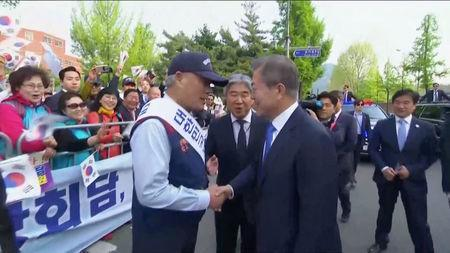 South Korean President Moon Jae-in shakes hands in Seoul, as he makes his way to the inter-Korean summit, in this still frame taken from video, April 27, 2018. Host Broadcaster via REUTERS TV
