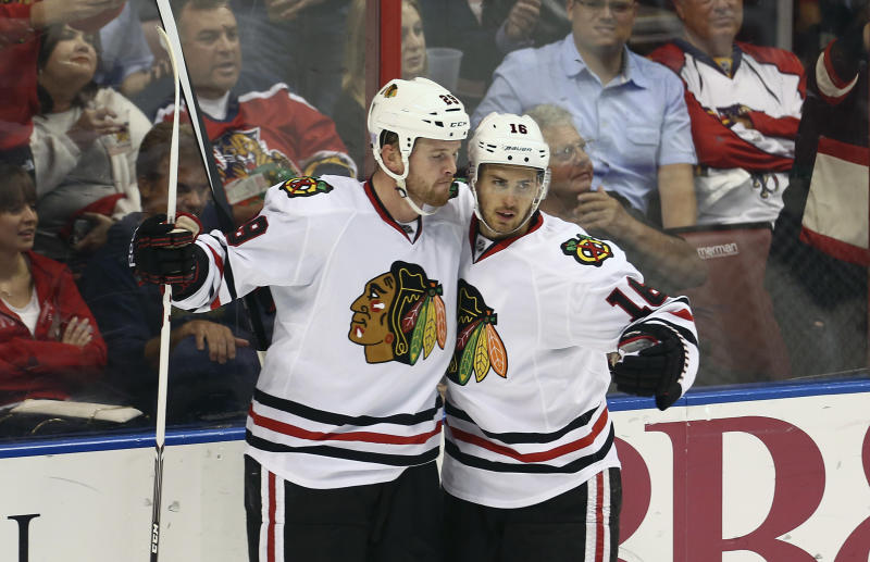 Chicago Blackhawks players Ben Smith (28) and Marcus Kruger celebrate after a goal scored against the Florida Panthers during the second period of an NHL hockey game in Sunrise, Fla., Tuesday, Oct. 22, 2013. (AP Photo/J Pat Carter)