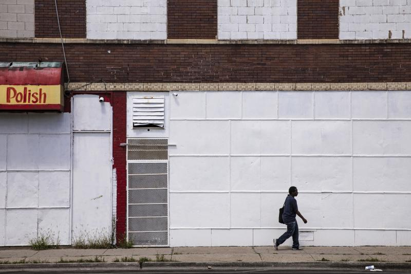 In this Friday, Aug. 9, 2019, photo, a man walks on a sidewalk past boarded up business in Chicago's Englewood neighborhood. As of 2015, roughly 22% of Atlanta's population was living in a low-income community more than a mile from a food store, and in Chicago, that number is 5%, according to the U.S. Department of Agriculture. (AP Photo/Amr Alfiky)