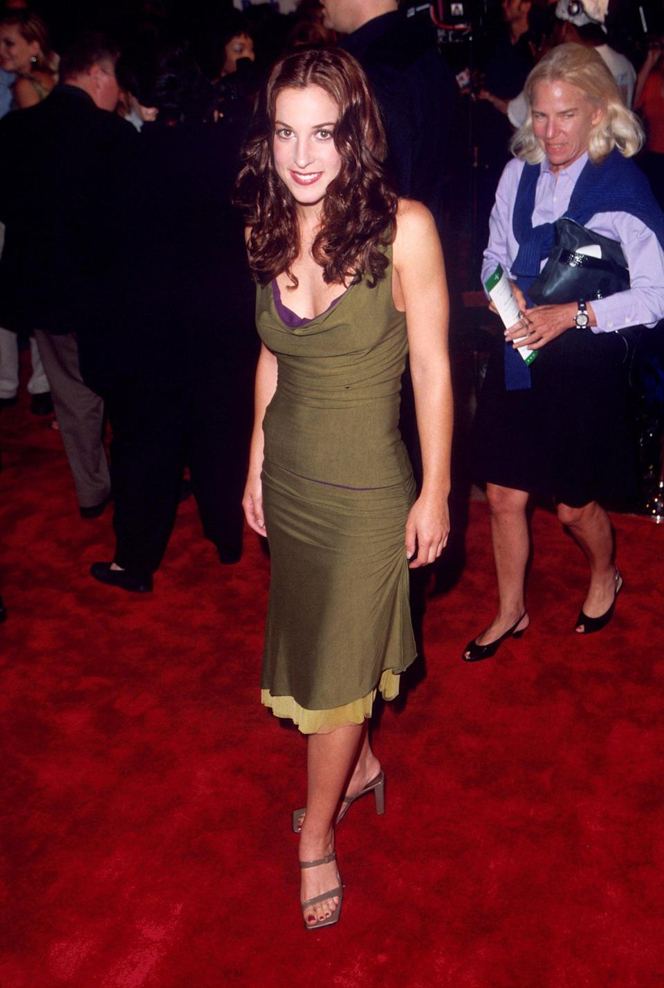 """<p>""""Big Red"""" arrived to the premiere in a slinky olive co-ord set that she wore with taupe, square-toed sandals. The neutrals might not have been as bright as some of the other looks, but these silhouettes were prominent in the early 2000s.</p>"""