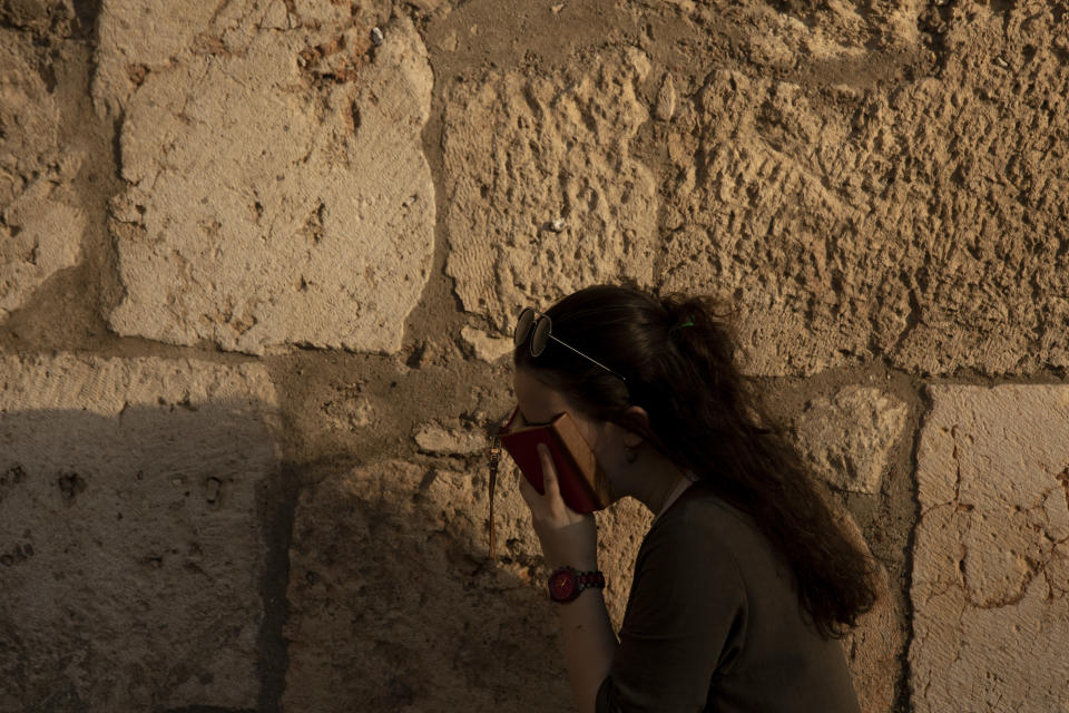 A woman prays at the Western Wall, the holiest site where Jews can pray, in the shadow of the Mughrabi Bridge, a wooden pedestrian bridge connecting the wall to the Al Aqsa Mosque compound, in Jerusalem's Old City, Tuesday, July 20, 2021. The rickety bridge allowing access to Jerusalem's most sensitive holy site is at risk of collapse, according to experts. But the flashpoint shrine's delicate position at ground-zero of the Israeli-Palestinian conflict has prevented its repair for more than a decade. (AP Photo/Maya Alleruzzo)