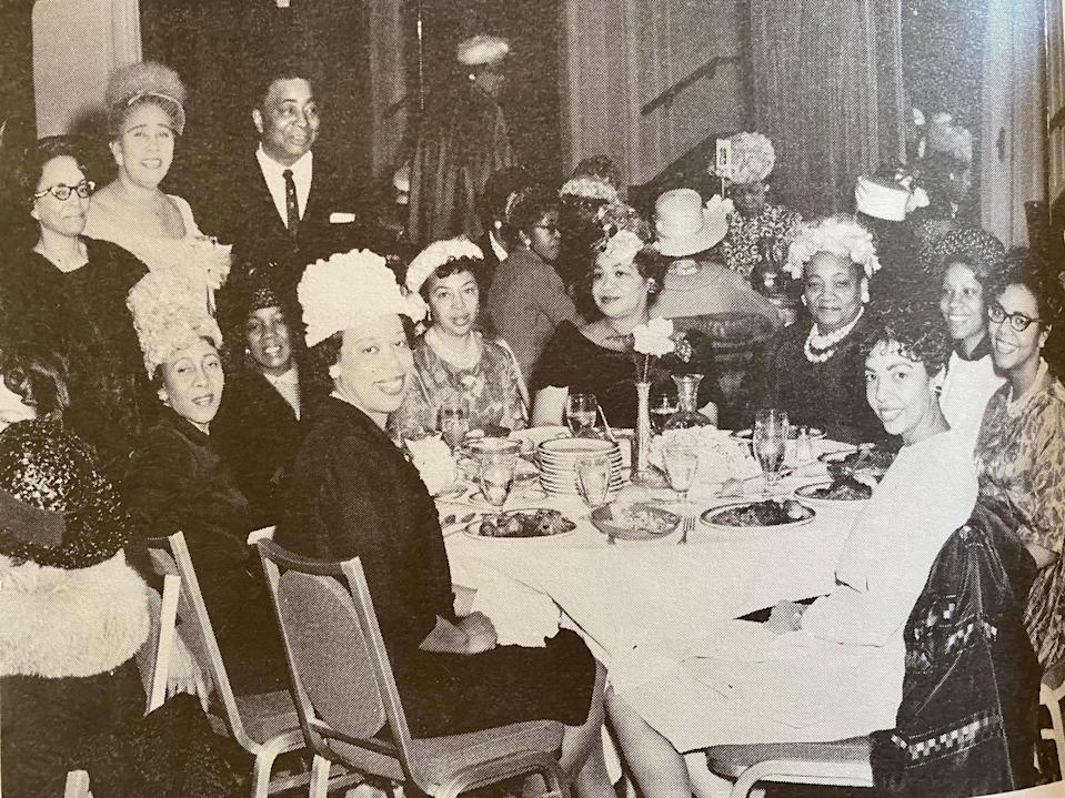 in a black and white photo, people in fancy outfits pose at a dinner table