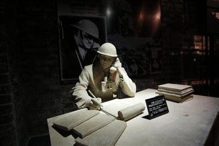 """A model and a photograph of John Rabe, sometimes call """"China's Schindler"""", are seen in a museum, during a reporting trip in Nanjing, Jiangsu province February 19, 2014. REUTERS/Aly Song"""