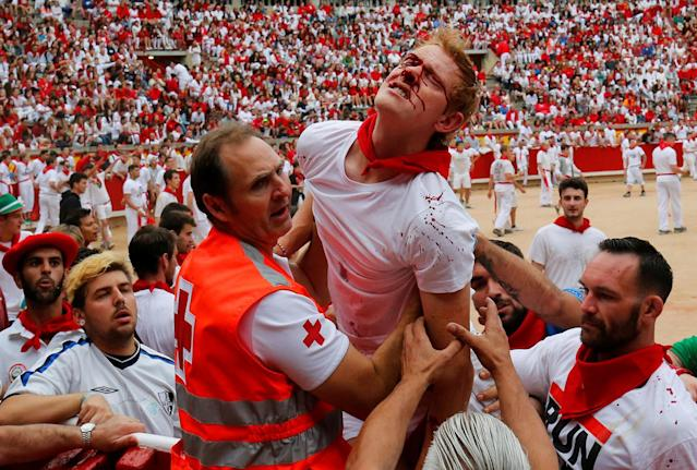 <p>A reveller injured by a wild cow is taken away from the bullring following the seventh running of the bulls at the San Fermin festival in Pamplona, northern Spain, July 13, 2017. (Photo: Susana Vera/Reuters) </p>
