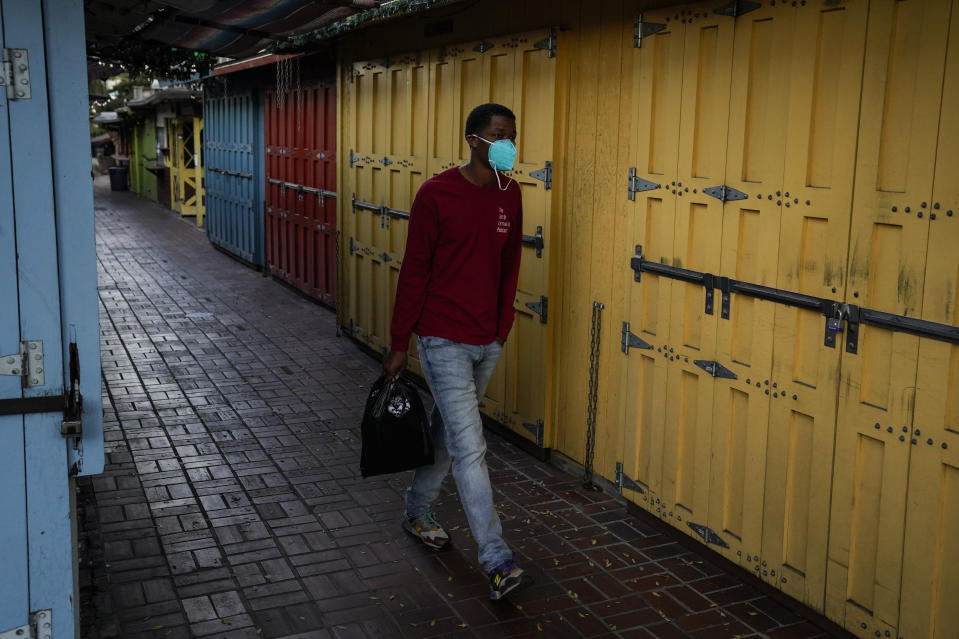 A man wearing a face mask walks past shuttered market stalls on empty Olvera Street in downtown Los Angeles, Tuesday, Dec. 15, 2020. The tree-covered brick alley typically teeming with tourists is empty. Many of the shops that sell everything from traditional Mexican folk dresses to paintings of artist Frida Kahlo to sombreros are padlocked and the ones open have few, if any, customers. (AP Photo/Jae C. Hong)