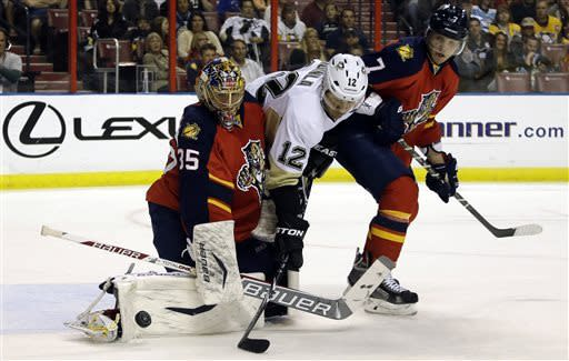 Pittsburgh Penguins' Jarome Iginla (12) attempts a shot on the goal as Florida Panthers goalie Jacob Markstrom (35) defends during the first period of a hockey game, Saturday, April 13, 2013, in Sunrise, Fla. At right is Florida Panthers' Dmitry Kulikov (7). (AP Photo/Lynne Sladky)