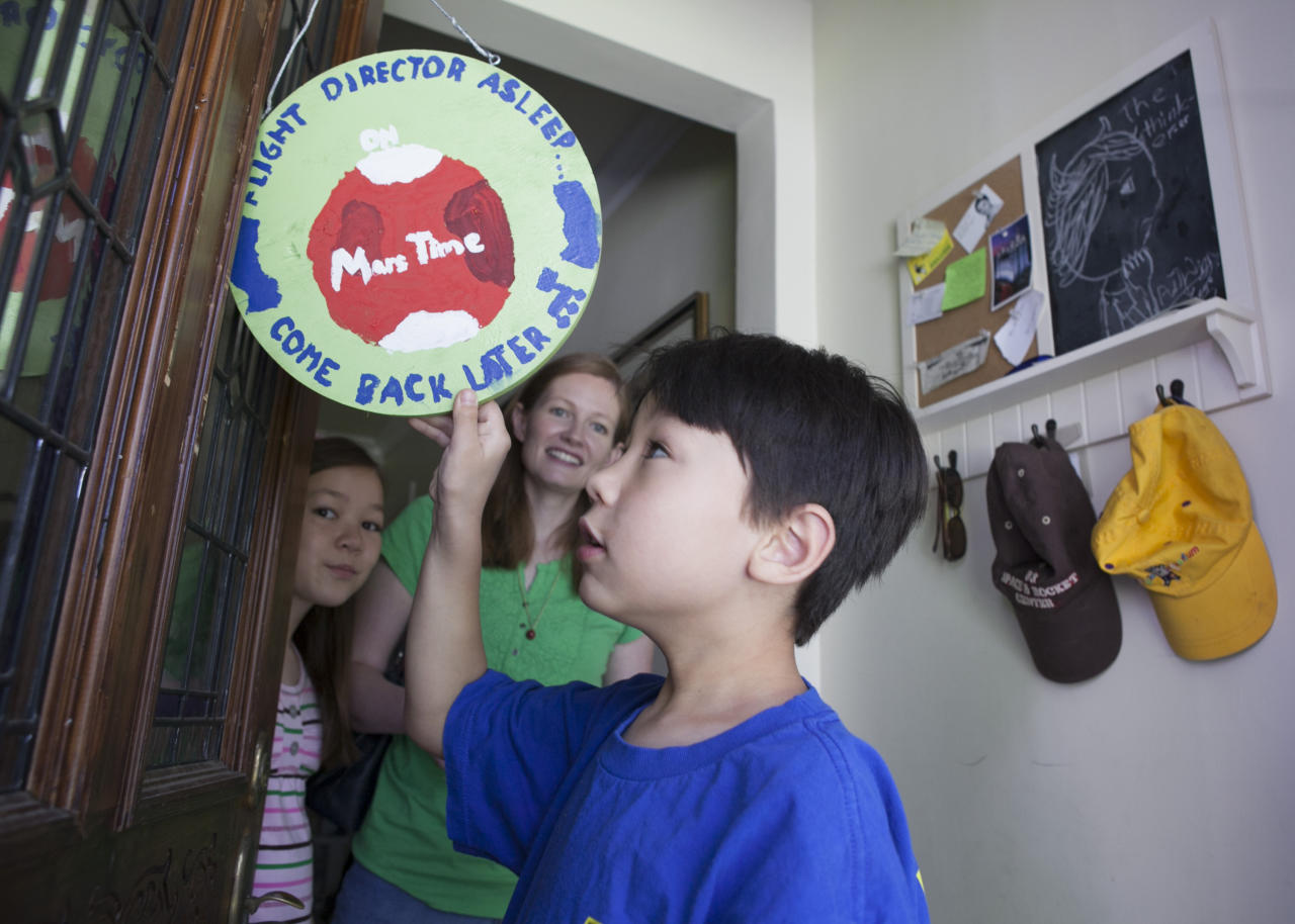 """In this photo taken Tuesday, Aug. 14, 2012, Devyn Oh, 8, flips around a sign reading: """"Flight Director Sleep on Mars Time, Come Back Later,"""" posted on their front door for his father, David Oh, a flight director of NASA's latest Mars mission, at their home in La Canada Flintridge, Calif. The Oh family has been living on Mars time and following an odd schedule ever since the NASA rover Curiosity landed in an ancient Martian crater on Aug. 5. Ashlyn Oh and their mother Bryn look on. (AP Photo/Damian Dovarganes)"""