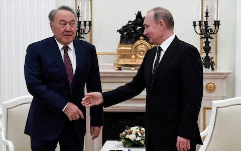 Mr Nazarbayev meets with Vladimir Putin in December. He has tried to gently assert Kazakhstan's independence from its former overlord - Credit: Alexander Nemenov/Pool Photo via AP