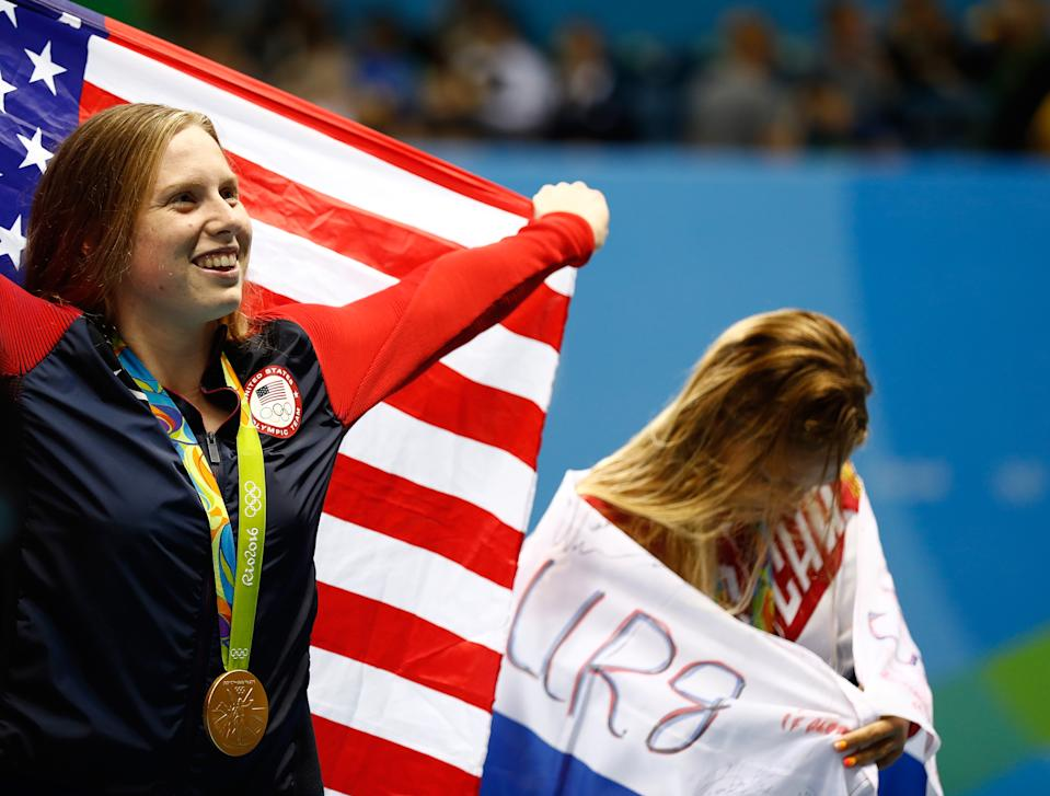 RIO DE JANEIRO, BRAZIL - AUGUST 08:  Gold medalist Lilly King of the United States celebrates as silver medalist Yulia Efimova of Russia looks on during the medal ceremony for the Women's 100m Breaststroke Final on Day 3 of the Rio 2016 Olympic Games at the Olympic Aquatics Stadium on August 8, 2016 in Rio de Janeiro, Brazil.  (Photo by Clive Rose/Getty Images)