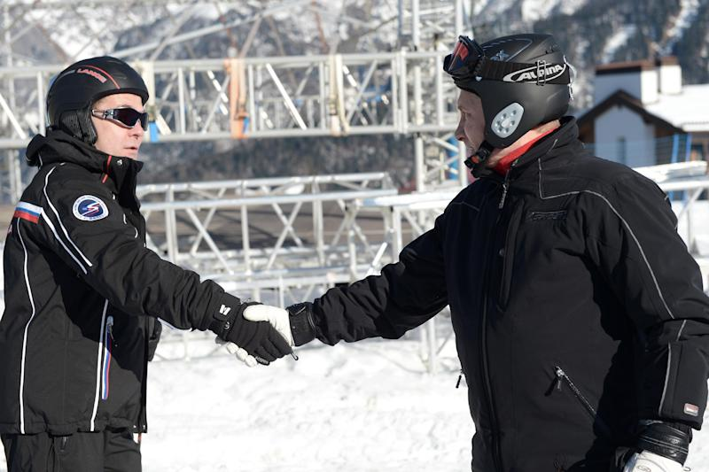 Russian President Vladimir Putin, right, shakes hands with Prime Minister Dmitry Medvedev as they prepare to ski in the mountain resort of Krasnaya Polyana near the Black Sea resort of Sochi, southern Russia, Friday, Jan. 3, 2014. (AP Photo/RIA-Novosti, Alexei Nikolsky, Presidential Press Service)