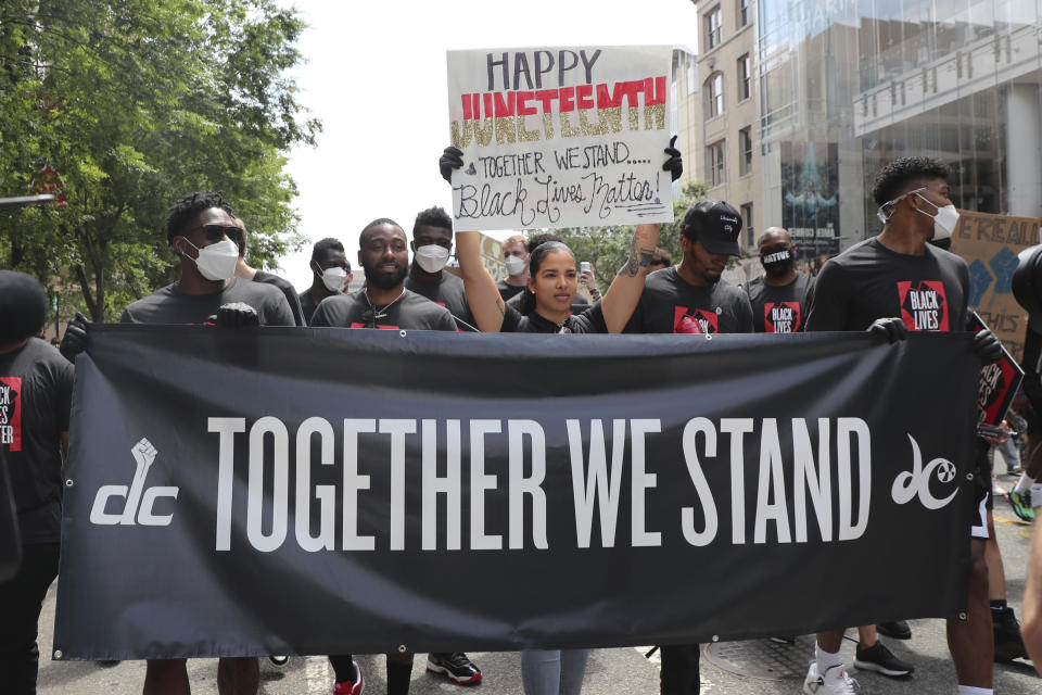 The Washington Mystics' Natasha Cloud is joined by the Washington Wizards' John Wall and Bradley Beal for a Black Lives Matter march down the streets of D.C. to the MLK Memorial. They are holding a black sign that says