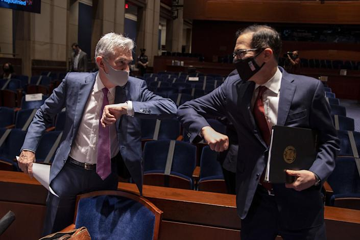 Federal Reserve Chairman Jerome Powell (left) and Treasury Secretary Steven Mnuchin bump elbows at the conclusion of a June 30 House Committee on Financial Services hearing on the pandemic response. (Photo: TASOS KATOPODIS/pool/AFP via Getty Images)