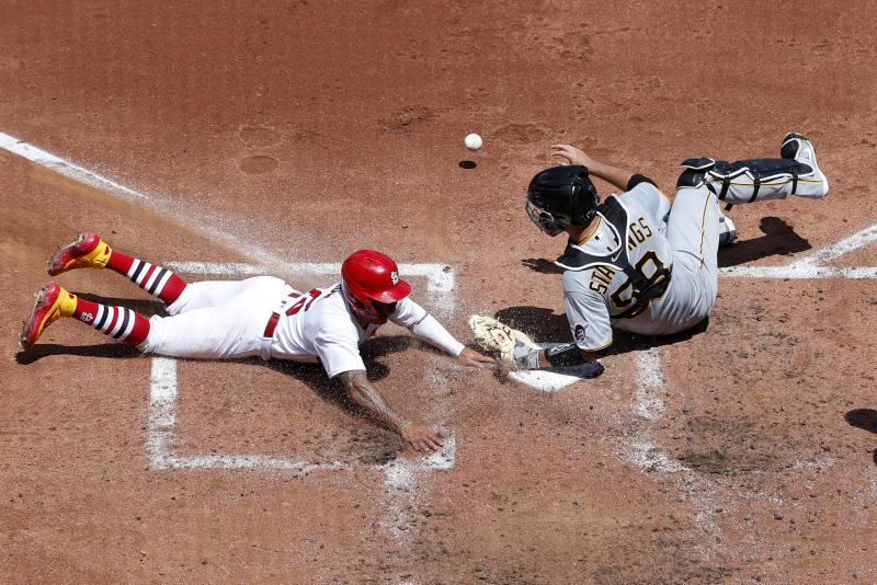 St. Louis Cardinals' Kolten Wong, left, scores as Pittsburgh Pirates catcher Jacob Stallings drops the ball during the third inning of a baseball game Sunday, July 26, 2020, in St. Louis. (AP Photo/Jeff Roberson)