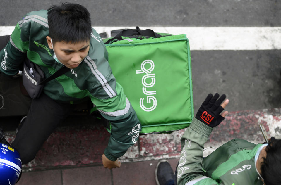 BANGKOK, THAILAND - 2021/04/20: A Grab motorcycle rider seen making delivery. During the Covid-19 pandemic the Grab home food delivery service network has expanded with thousands of former motorcycle taxi riders nationwide changing to the Grab delivery service via the online Grab App. Customers can order their favorite Thai and western foods online from a variety of local and popular restaurants in Bangkok. (Photo by Paul Lakatos/SOPA Images/LightRocket via Getty Images)