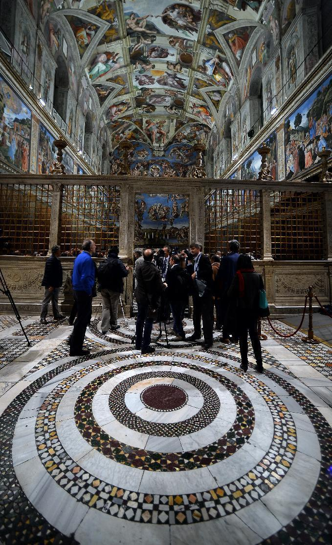 Journalists get a good look at the roof of the Sistine Chapel, lit up by 7,000 LED lamps designed specifically for its prized frescoes (AFP Photo/Filippo Monteforte)