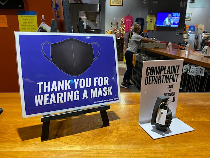 """Wearing a mask, a worker at Dodge City Brewing in Kansas cleans the bar behind a sign reminding customers they are required to wear a mask inside when not eating or drinking, next to a """"complaint department"""" sign with a mock grenade."""