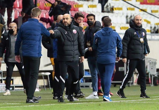 Qatar manager Felix Sanchez, centre, bumps fists with Stephen Kenny after the final whistle