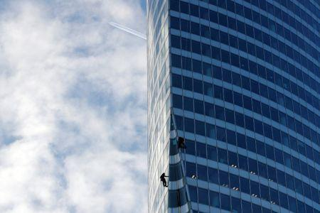 Workers climb the EDF tower, France's state-owned electricity company building, to check the structure in La Defense