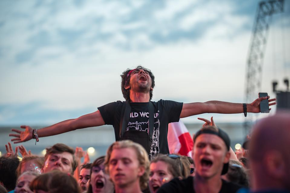 People waving flags and holding flares, and general atmosphere of the Reading Festival 2017 are pictured at Reading, on August 27, 2017. The Reading and Leeds Festivals are a pair of annual rock music festivals that take place in Reading and Leeds in England. The events take place simultaneously on the Friday, Saturday and Sunday of the August bank holiday weekend, sharing the same bill. (Photo by Alberto Pezzali/NurPhoto via Getty Images)