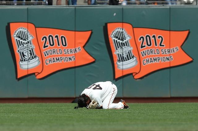 Jarrett Parker of the San Francisco Giants falls to the ground after making a catch against the outfield wall in the fourth inning against the Colorado Rockies at AT&T Park on April 15, 2017 (AFP Photo/Lachlan Cunningham)