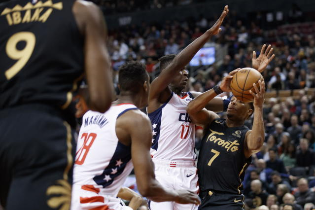 Toronto Raptors guard Kyle Lowry (7) is defended by Washington Wizards guard Isaac Bonga (17) and center Ian Mahinmi (28) during the first half of an NBA basketball game Friday, Jan. 17, 2020, in Toronto. (Cole Burston/The Canadian Press via AP)
