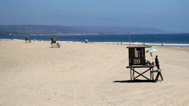 PHOTO: Lifeguards keep a lookout on a mostly empty beach, May 3, 2020, in Newport Beach, Calif. (Marcio Jose Sanchez/AP)