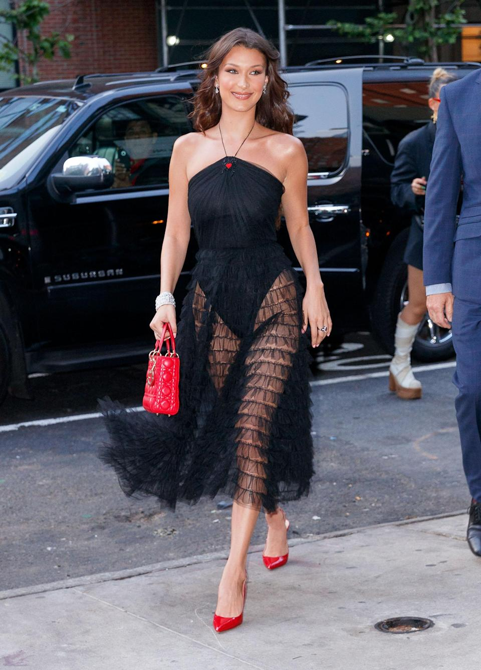 <p>Supermodel Bella Hadid not only debuted long extensions but rocked a new Dior dress featuring a sheet skirt while out in New York, which she wore with red accessories. <br><em>[Photo: Getty]</em> </p>