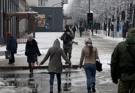 Armed men wearing masks block off a street in the centre of rebel-controlled city of Luhansk