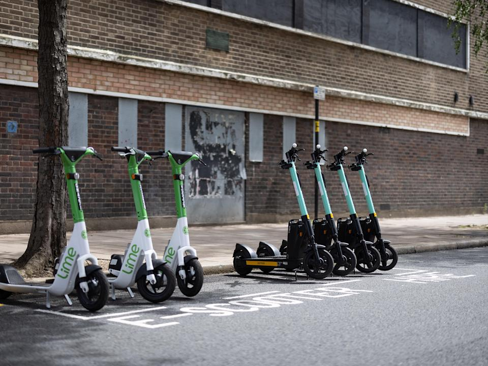 A row of both Lime (L) and Tier (R) electric scooters are seen in a parking bay on July 05, 2021 in London, England. (Getty Images)