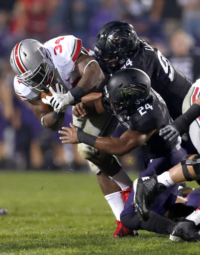 Ohio State running back Carlos Hyde (34) carries the ball and is tackled by Northwestern defensive lineman Dean Lowry (94) and safety Ibraheim Campbell during the first half of an NCAA football game on Saturday, Oct. 5, 2013, in Evanston, Ill. (AP Photo/Charles Rex Arbogast)