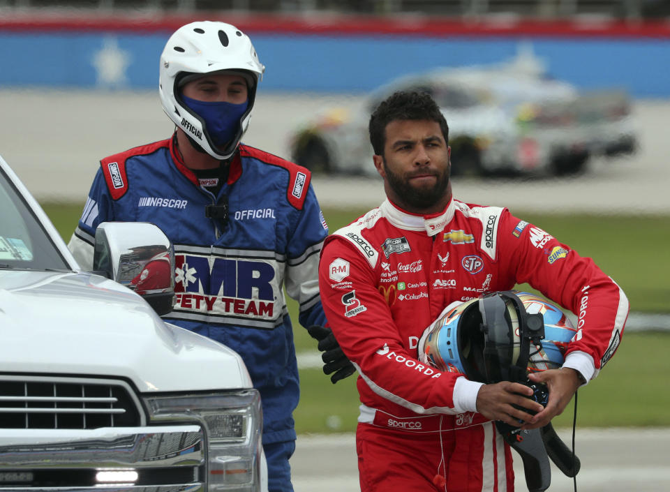 FILE - Bubba Wallace walks away from his damaged car, next to a NASCAR Safety Team member, during the NASCAR Cup Series auto race at Texas Motor Speedway in Fort Worth, Texas, Wednesday, Oct. 28, 2020. Wallace has been named the Comcast Community Champion of the Year. The industry award honors NASCAR members for philanthropic efforts. (AP Photo/Richard W. Rodriguez, File)