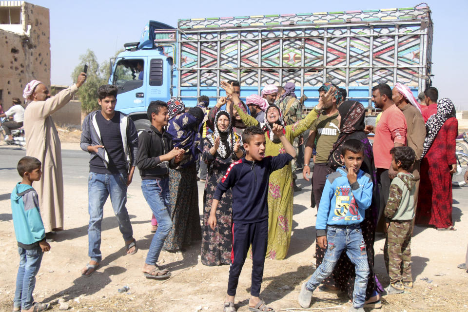 People welcome Syrian troops as they enter the village of Ghebesh, west of the town of Tal Tamr, in northern Syria, Monday, Oct 14, 2019. Syrian government troops moved into towns and villages in northern Syria on Monday, setting up a potential clash with Turkish-led forces advancing in the area as long-standing alliances in the region begin to crumble following the pullback of U.S. forces. (AP Photo)