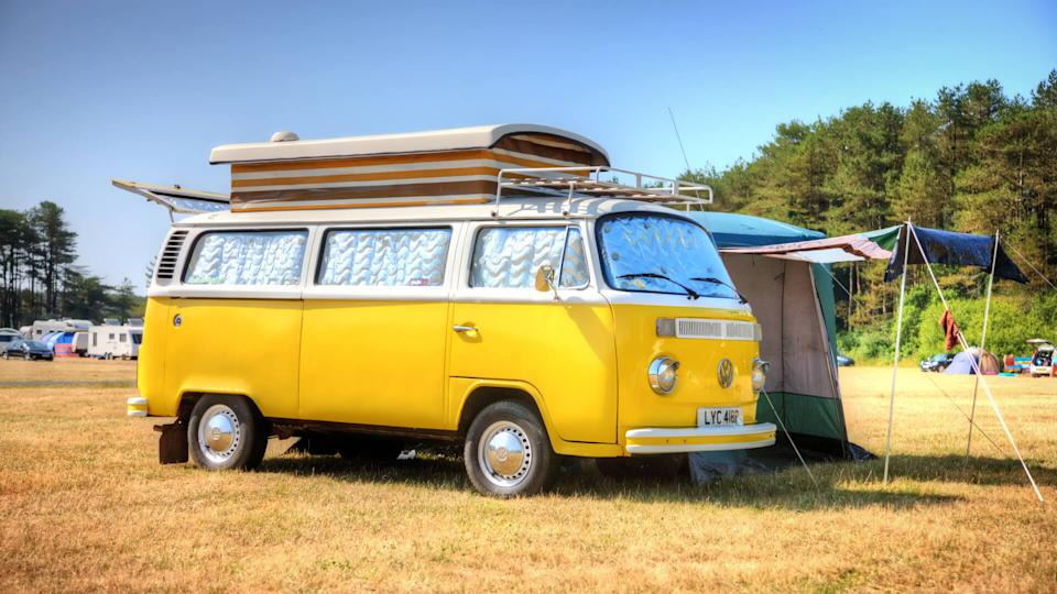 Pembrey, Wales - July 13, 2013: Old fashioned VW campervan on Welsh campsite with canvas awning attached.