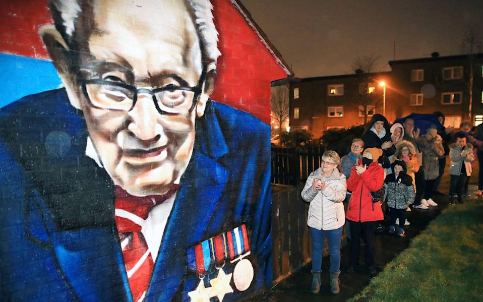 Local residents join a national clap beside a mural of Captain Sir Tom Moore in East Belfast, Northern Ireland, Wednesday - AP Photo/Peter Morrison