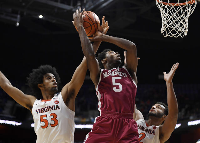 Virginia's Tomas Woldetensae (53) fouls Massachusetts' Samba Diallo (5) as Virginia's Braxton Key (2) defends during the first half of an NCAA college basketball game, Saturday, Nov. 23, 2019, in Uncasville, Conn. (AP Photo/Jessica Hill)