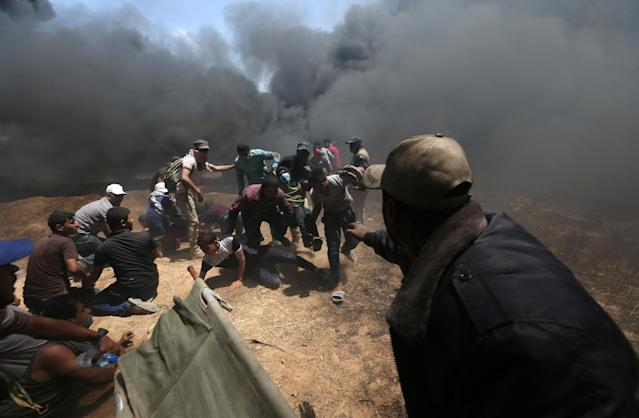 A wounded Palestinian demonstrator is evacuated as others take cover from Israeli fire and tear gas during a protest against the U.S. Embassy move to Jerusalem and ahead of the 70th anniversary of Nakba, at the Israel-Gaza border in the southern Gaza Strip May 14, 2018. (Photo: Ibraheem Abu Mustafa/Reuters)