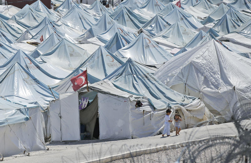 Children walk past tents of a Syrian refugees camp in Yayladagi, Turkey, Tuesday, Sept. 3, 2013. The civil war in Syria has forced over 2 million people out of the country and over 4 million others are displaced within its borders, making Syrians the nation with the largest number of people torn from their homes, U.N. officials said Tuesday. (AP Photo/Gregorio Borgia)