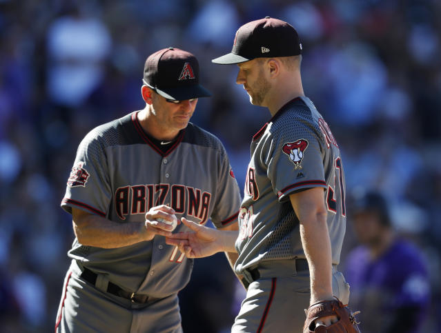 Arizona Diamondbacks manager Torey Lovullo, left, takes the ball from relief pitcher Brad Boxberger who is pulled from the mound after getting Colorado Rockies' Chris Iannetta to fly out in the seventh inning of a baseball game Thursday, Sept. 13, 2018, in Denver. (AP Photo/David Zalubowski)