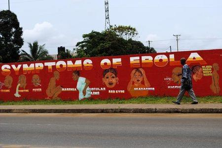 """A man walks by a mural that reads """"Symptoms of Ebola"""" in Monrovia"""