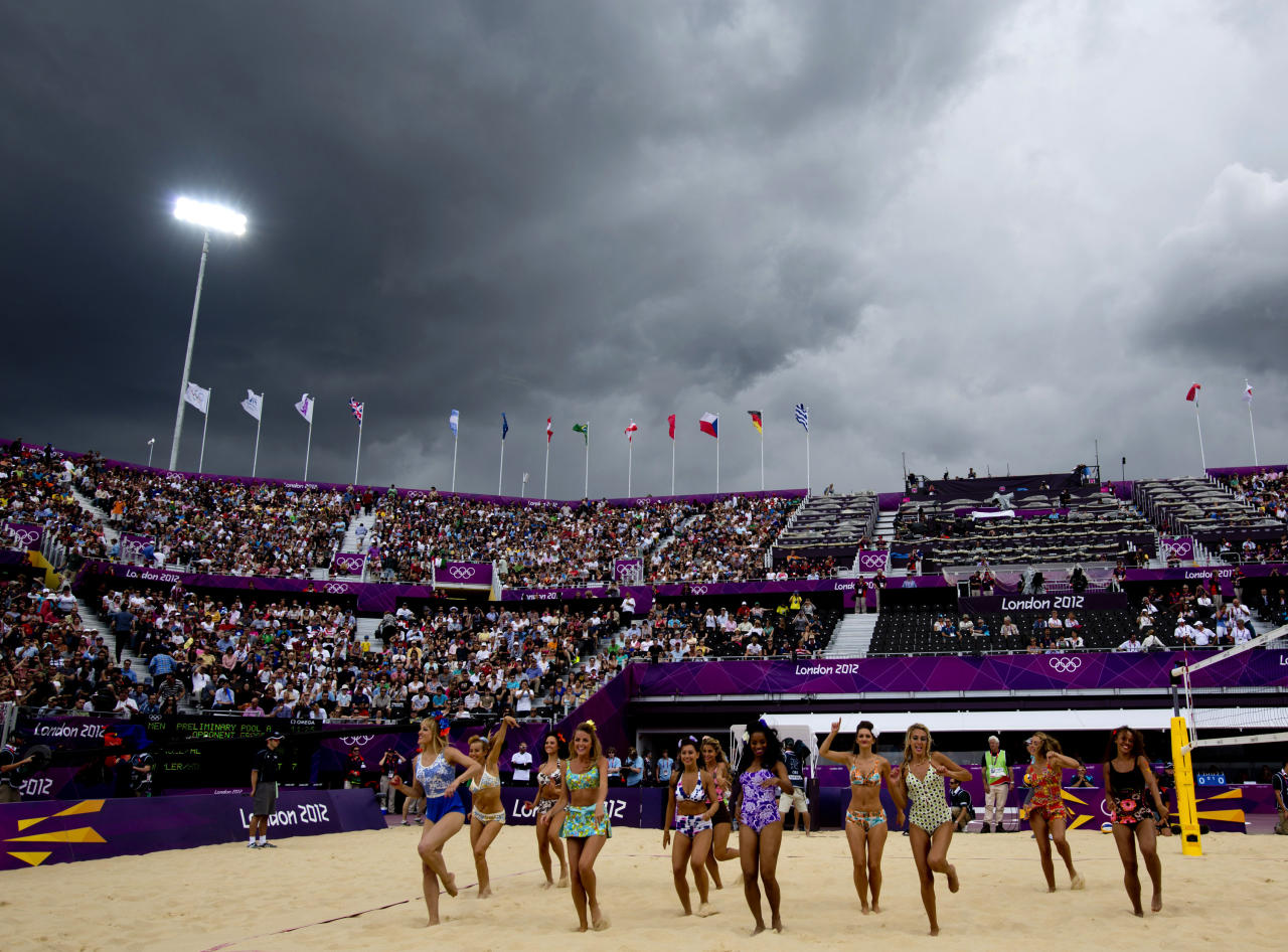 Rain clouds gather as dancers entertain spectators at the Horse Guards Parade before a Beach Volleyball match in London July 29, 2012. REUTERS/Neil Hall (BRITAIN - Tags: SPORT VOLLEYBALL OLYMPICS ENVIRONMENT)